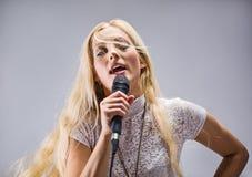 Frau, die in ein Mikrofon singt Stockbild
