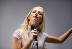 Frau, die in ein Mikrofon singt lizenzfreie stockfotos