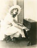 Frau, die ein Miniaturklavier spielt Stockbild