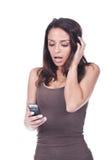 Frau, die ein Mobiltelefon anhält und überrascht schaut lizenzfreies stockfoto