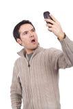 Frau, die ein Mobiltelefon anhält und überrascht schaut stockbild