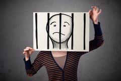 Frau, die ein Papier mit einem Gefangenen hinter den Stangen auf ihm in f hält Stockfotografie