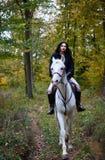 Frau, die ein Pferd im Wald reitet Lizenzfreies Stockfoto