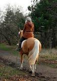 Frau, die ein Pferd reitet Lizenzfreie Stockfotos