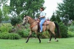 Frau, die ein Pferd reitet Lizenzfreie Stockbilder