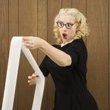 Frau, die ein PRINTOUT mit einem schokierenden Ausdruck auf ihrem Gesicht anhält. Stockfotos