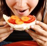 Frau, die ein Sandwich isst Lizenzfreie Stockfotografie