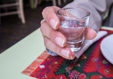 Frau, die ein Schnapsglas im Restaurant hält lizenzfreie stockbilder