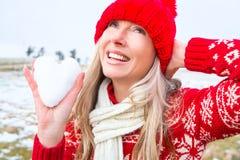 Frau, die ein Schneeherz hält Weihnachts- oder Winterthema lizenzfreies stockbild