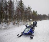 Frau, die ein Schneemobile in Ruka von Lappland handhabt Stockfotos