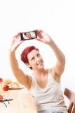 Frau, die ein Selbstporträt mit ihrem Smartphone macht Lizenzfreie Stockbilder