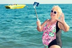 Frau, die ein selfie an einem Handy auf dem Strand nimmt Krasnodar Gegend, Katya lizenzfreie stockfotografie