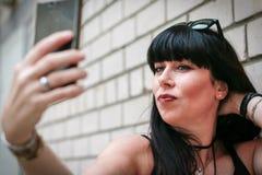 Frau, die ein selfie nahe einer Wand nimmt Stockfotografie
