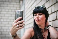 Frau, die ein selfie nahe einer Wand nimmt Lizenzfreies Stockfoto