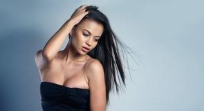 Frau, die ein sexy schwarzes Kleid trägt Stockbild