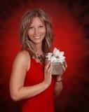 Frau, die ein silbernes Geschenk anhält stockfoto