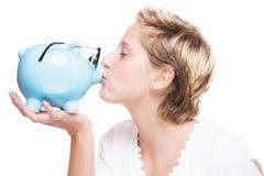 Frau, die ein Sparschwein küsst Stockfotos