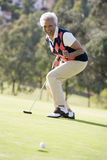 Frau, die ein Spiel des Golfs spielt Lizenzfreie Stockbilder