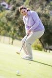 Frau, die ein Spiel des Golfs spielt Stockbild