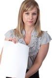 Frau, die ein unbelegtes Blatt Papier anhält Lizenzfreie Stockfotos