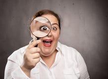 Frau, die ein Vergrößerungsglas anhält lizenzfreie stockbilder
