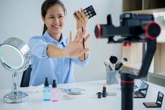 Frau, die ein Video für ihr Blog auf Kosmetik unter Verwendung des digitalen Nockens herstellt Lizenzfreies Stockbild