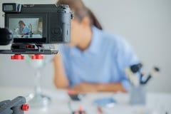 Frau, die ein Video für ihr Blog auf Kosmetik unter Verwendung des digitalen Nockens herstellt Lizenzfreie Stockbilder