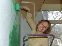 Frau, die ein Wandgrün malt Lizenzfreies Stockfoto