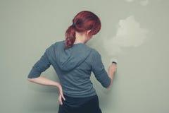Frau, die ein Wandgrün malt Stockfoto