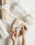 Frau, die ein Weihnachtsgeschenk bindet Stockbild