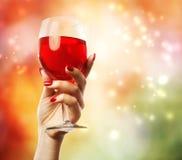 Frau, die ein Weinglas anhält Stockfotografie