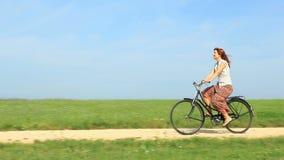 Frau, die ein Weinlesefahrrad auf einen Frühlingsmorgen reitet stock video