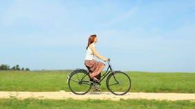Frau, die ein Weinlesefahrrad auf einen Frühlingsmorgen reitet stock video footage