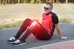 Frau, die ein wundes Knie anhält lizenzfreies stockfoto