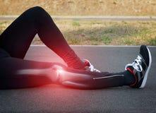 Frau, die ein wundes Knie anhält Lizenzfreie Stockfotos