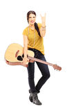 Frau, die eine Akustikgitarre hält und einen Rock-and-Roll Sig gibt Lizenzfreie Stockfotos