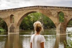 Frau, die eine alte Brücke betrachtet stockfotografie