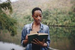 Frau, die eine Anmeldung im Wald liest stockfotos