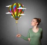 Frau, die eine Ballonzeichnung hält Lizenzfreie Stockbilder