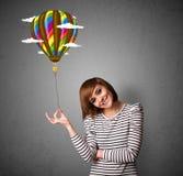 Frau, die eine Ballonzeichnung hält Lizenzfreies Stockfoto