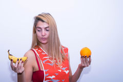 Frau, die eine Banane und eine Orange hält Stockbild