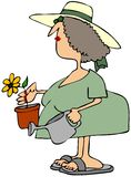 Frau, die eine Blume pflanzt Stockbilder