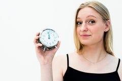 Frau, die eine Borduhr anhält Stockbild