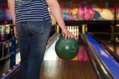 Frau, die eine Bowlingkugel am Bowlingspielverein hält Stockbilder