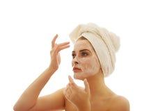 Frau, die eine Creme auf ihrem Gesicht aufträgt Lizenzfreie Stockbilder