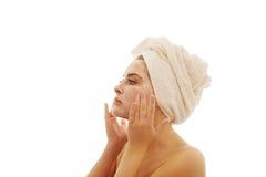 Frau, die eine Creme auf ihrem Gesicht aufträgt Stockbild