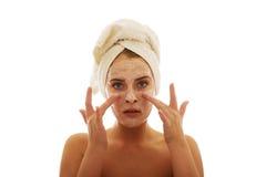 Frau, die eine Creme auf ihrem Gesicht aufträgt Lizenzfreies Stockbild