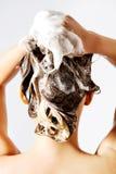 Frau, die eine Dusche nimmt und ihr Haar shampooing Auf Weiß Stockbild
