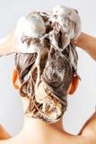 Frau, die eine Dusche nimmt und ihr Haar shampooing Lokalisiert auf Weiß Stockfotografie