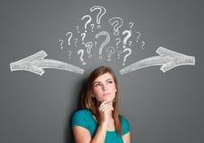 Frau, die eine Entscheidung mit Pfeilen und Fragezeichen über ihr trifft Stockfoto